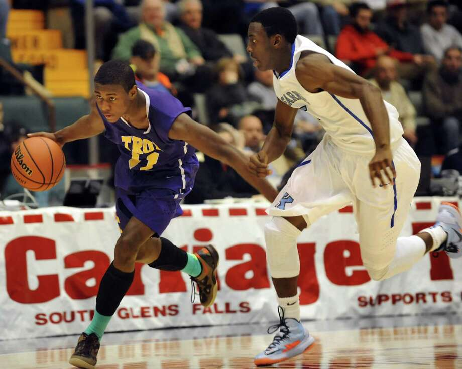 Troy's Dyaire Holt, left, drives up court as Bishop Kearney's Antwoine Anderson defends during their Class AA semifinal basketball game on Saturday, March 16, 2013, at Glens Falls Civic Center in Glens Falls , N.Y. (Cindy Schultz / Times Union) Photo: Cindy Schultz / 10021545A