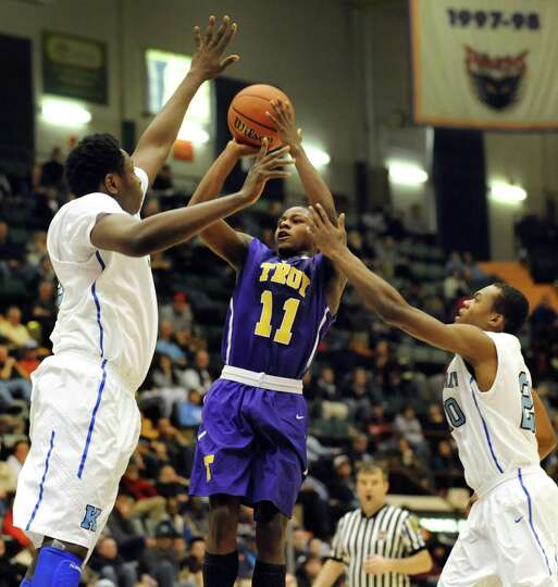 Troy's Dyaire Holt, center, tries to shoot as Bishop Kearney's Godspower Ogide, left, and Jwan Smith