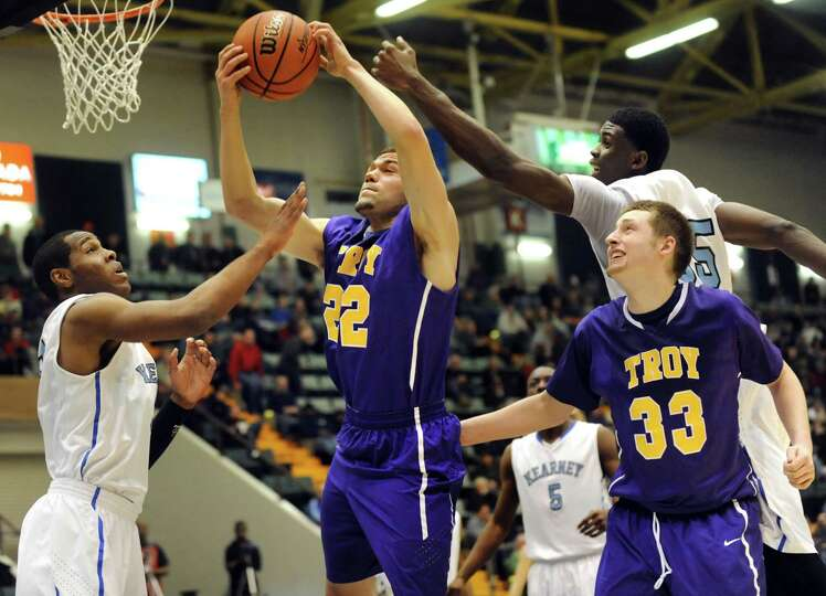 Troy's Imre Megyeri, center, grabs a rebound during their Class AA semifinal basketball game against