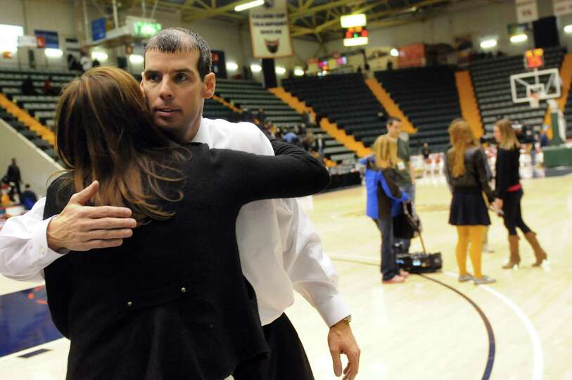 Troy's coach Richard Hurley, center, embraces his wife, Danielle, after their 65-58 loss to Bishop K
