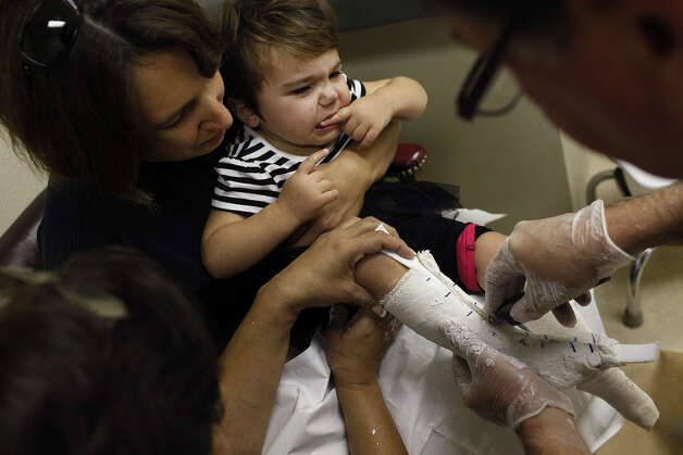 Crystal Bedford holds daughter Marley tightly as orthotist Dan Hughes makes casts for her new leg braces. Photo: Lisa Krantz / San Antonio Express-News