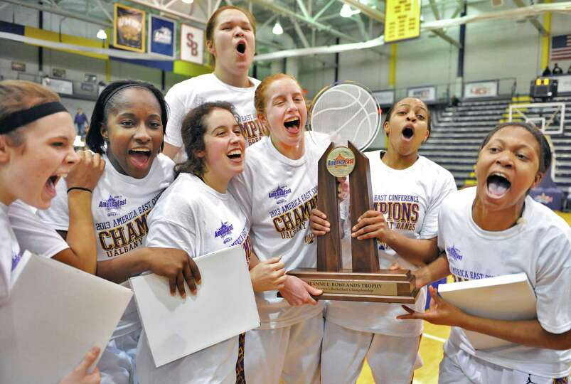 UAlbany women celebrate with the America East championship trophy after defeating Hartford in Albany