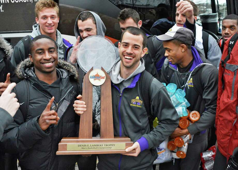 Players D.J. Evans, left, and Jacob Iati carry the trophy as the University at Albany men's basketball team returns to their campus after their NCAA Tournament victory over Vermont in the America East Conference championship game Saturday March 16, 2013.  (John Carl D'Annibale / Times Union) Photo: John Carl D'Annibale