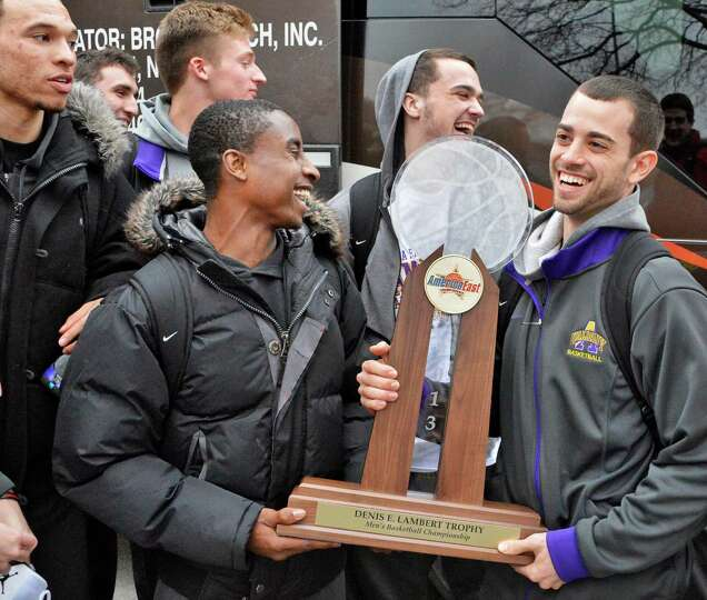 Players D.J. Evans, left, and Jacob Iati carry the trophy as the University at Albany men's basketba