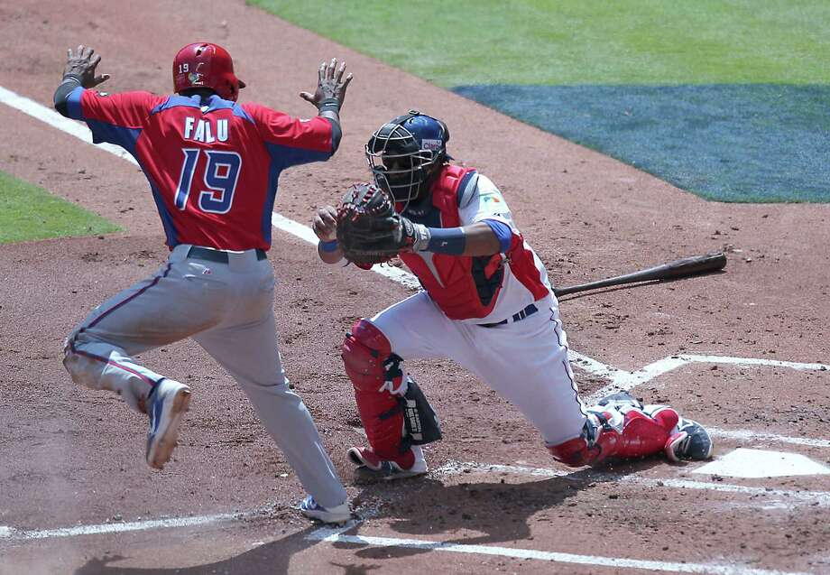 Puerto Rico pinch-runner Irving Falu is tagged out by Dominican catcher Carlos Santana in the third. Photo: David Santiago / El Nuevo Herald