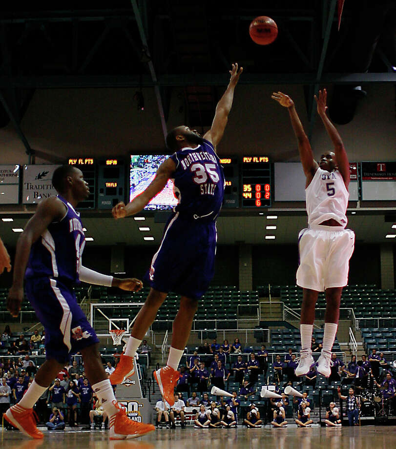 Stephen F. Austin's Antonio Bostic right, shoots the ball over Northwestern State's O.J. Evans center, and Gary Stewart left, during first half of the Southland Conference basketball tournament championship game at the Leonard E. Merrill Center Saturday, March 16, 2013, in Katy . Photo: James Nielsen, Houston Chronicle / © 2013 Houston Chronicle