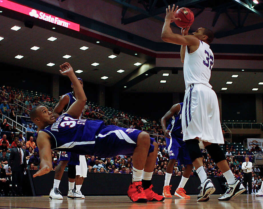 Stephen F. Austin's Taylor Smith right, shoots the ball over Northwestern State's DeQuan Hicks left, during first half of the Southland Conference basketball tournament championship game at the Leonard E. Merrill Center Saturday, March 16, 2013, in Katy . Photo: James Nielsen, Houston Chronicle / © 2013 Houston Chronicle