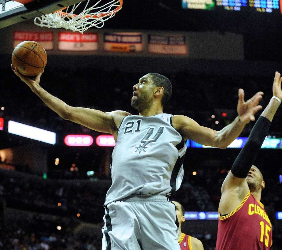 Tim Duncan of the Spurs scores on a reverse layup as Marreese Speights of the Cleveland Cavaliers defends at the AT&T Center on Saturday, March 16, 2013. Photo: Billy Calzada, San Antonio Express-News / San Antonio Express-News