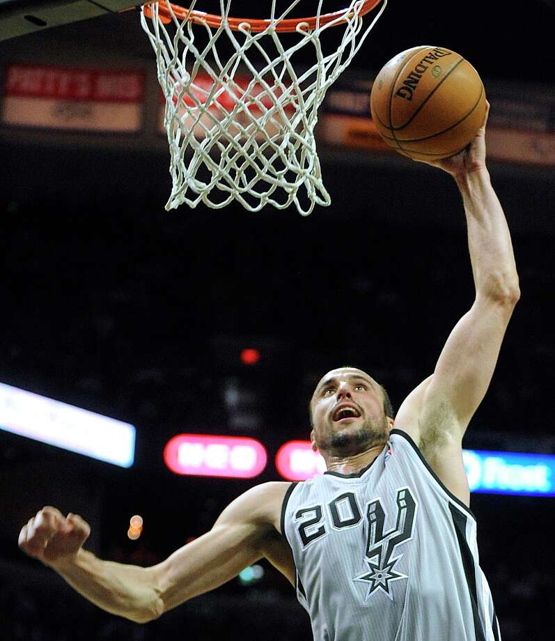 Manu Ginobili of the Spurs dunks against Cleveland during first-half action at the AT&T Center on Saturday, March 16, 2013. Photo: Billy Calzada, San Antonio Express-News / San Antonio Express-News