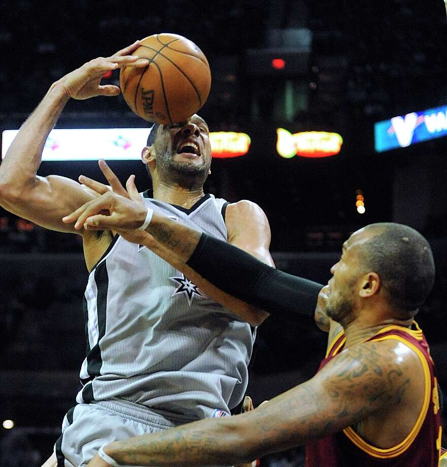 Tim Duncan battles for a loose ball against the Cleveland Cavaliers at the AT&T Center on Saturday, March 16, 2013. Photo: Billy Calzada, San Antonio Express-News / San Antonio Express-News