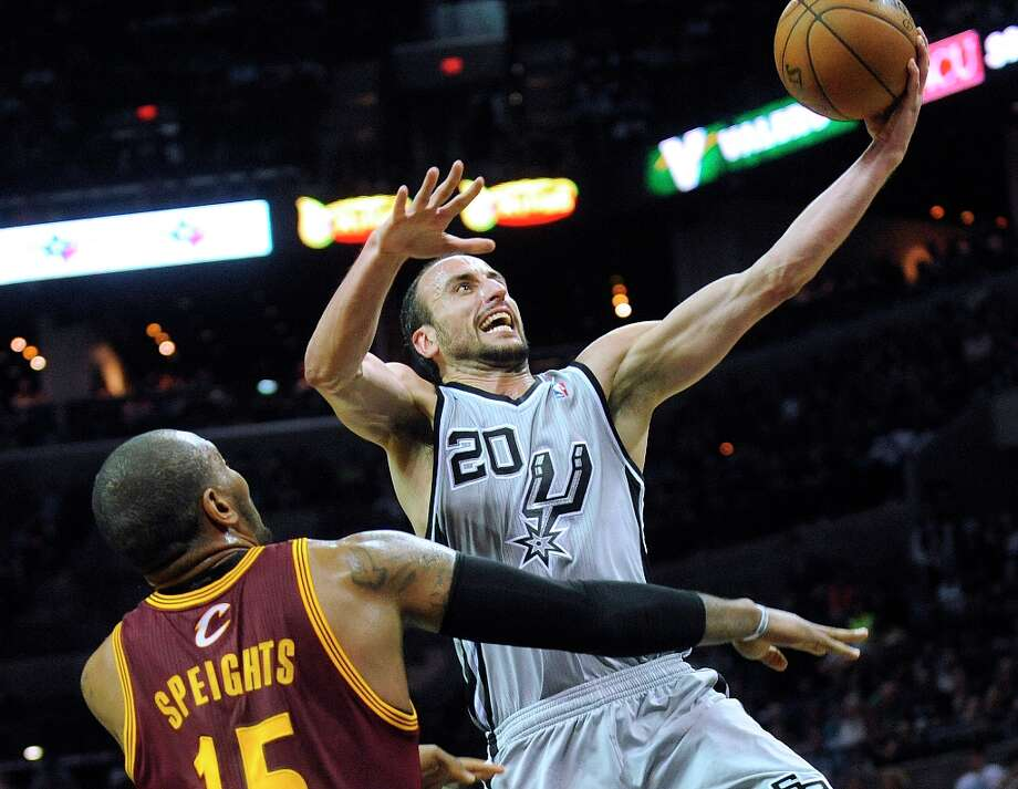 Manu Ginobili of the Spurs drives past Marreese Speights of the Cleveland Cavaliers during action at the AT&T Center on Saturday, March 16, 2013. Photo: Billy Calzada, San Antonio Express-News / San Antonio Express-News