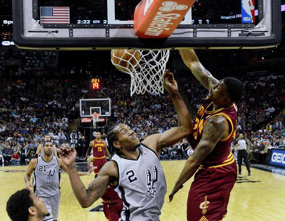 Alonzo Gee of the Cleveland Cavaliers dunks over Kawhi Leonard of the Spurs during second-half action at the AT&T Center on Saturday, March 16, 2013. Photo: Billy Calzada, San Antonio Express-News / San Antonio Express-News