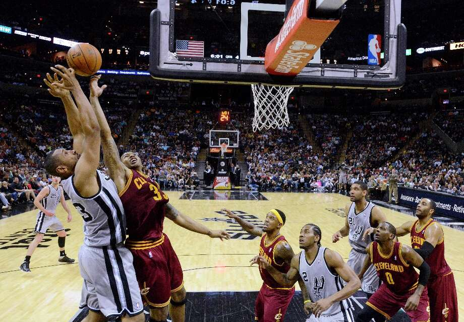 Boris Diaw (left) of the Spurs and Alonzo Gee of the Cavaliers fight for a rebound at the AT&T Center on Saturday, March 16, 2013. Photo: Billy Calzada, San Antonio Express-News / San Antonio Express-News