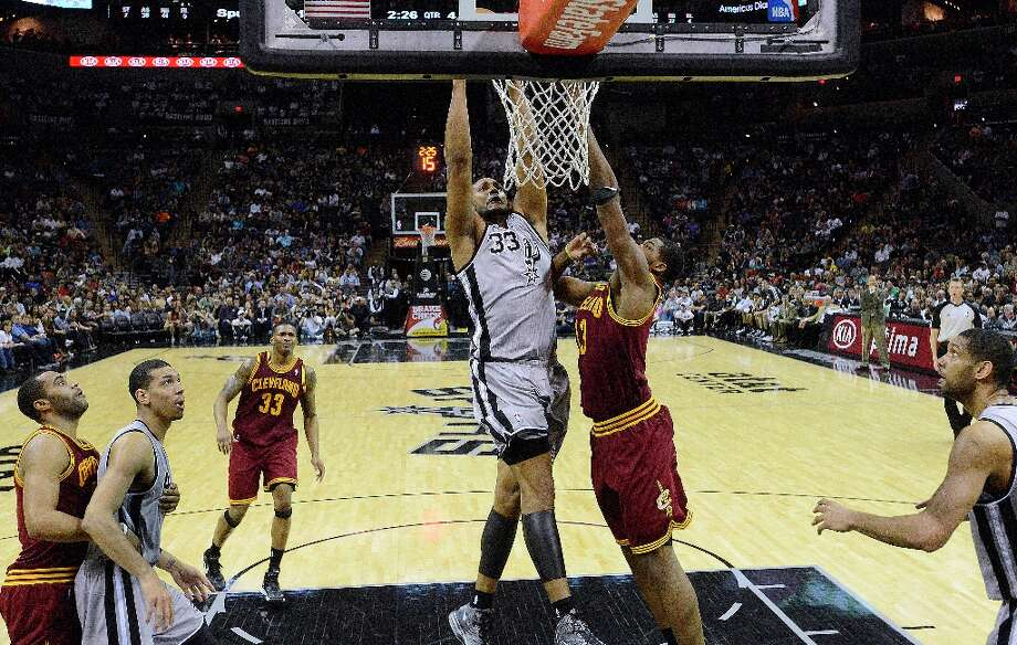 Boris Diaw of the Spurs dunks over Tristan Thompson of the Cleveland Cavaliers during second-half action at the AT&T Center on Saturday, March 16, 2013. Photo: Billy Calzada, San Antonio Express-News / San Antonio Express-News
