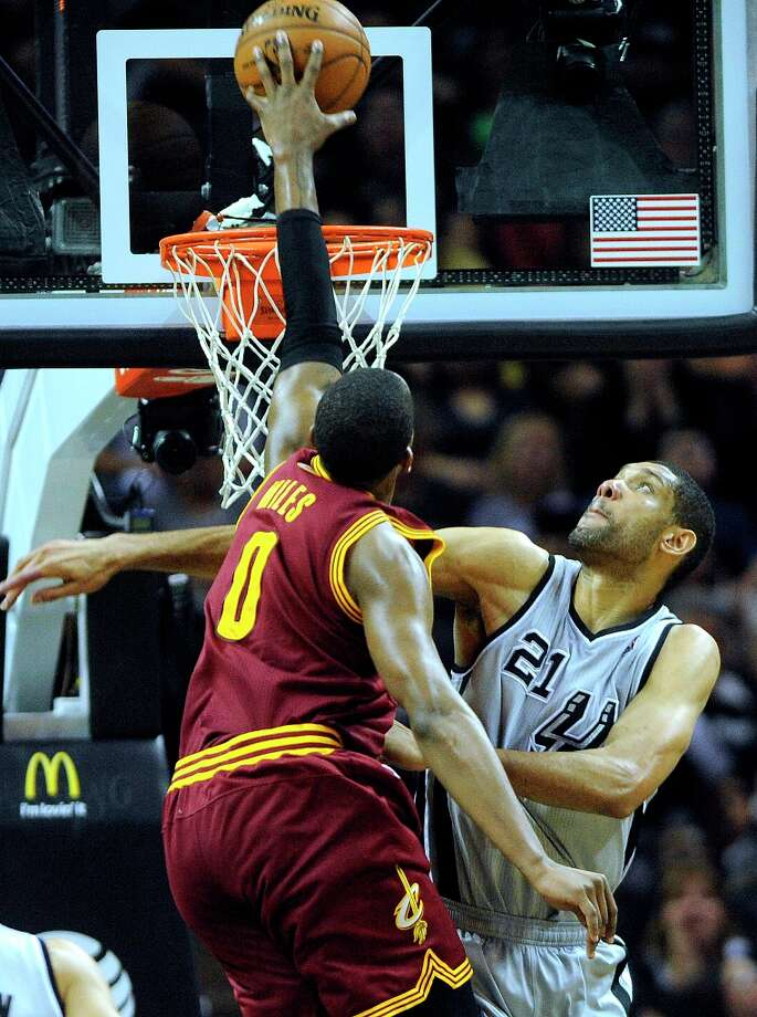 Tim Duncan of the Spurs spoils a dunk attempt by C.J. Miles of the Cleveland Cavaliers at the AT&T Center on Saturday, March 16, 2013. Photo: Billy Calzada, San Antonio Express-News / San Antonio Express-News