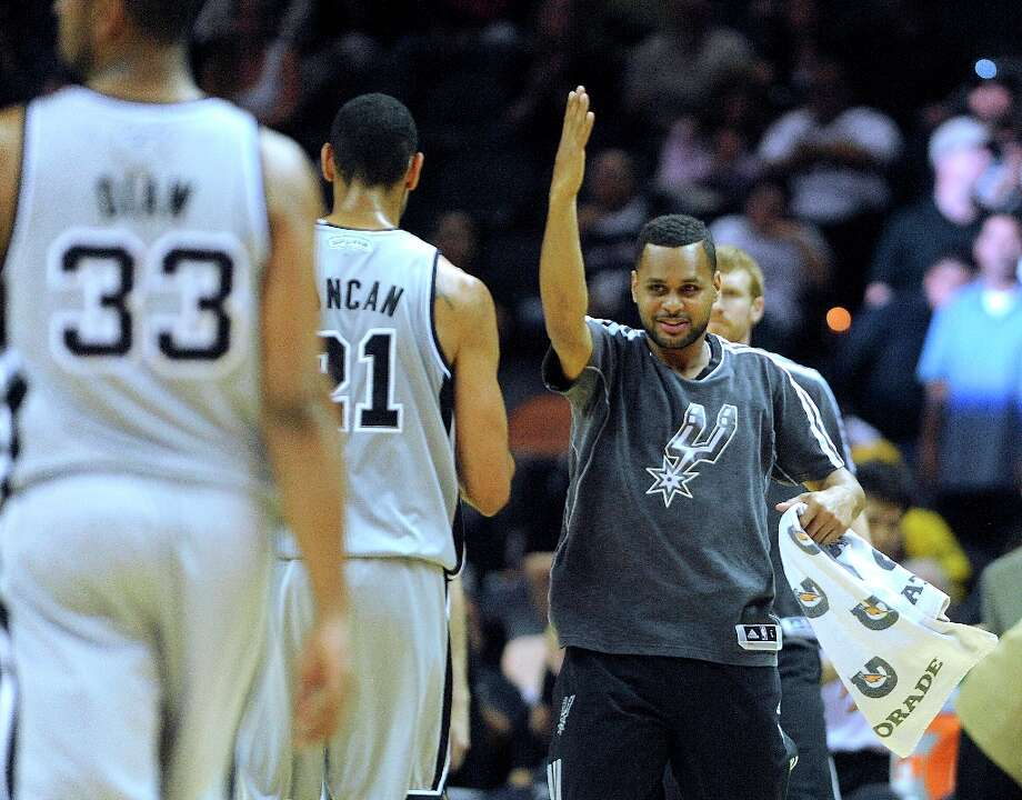 Patty Mills of the Spurs greets his teammates during a timeout of the team's victory over the Cleveland Cavaliers on Saturday, March 16, 2013. Photo: Billy Calzada, San Antonio Express-News / San Antonio Express-News