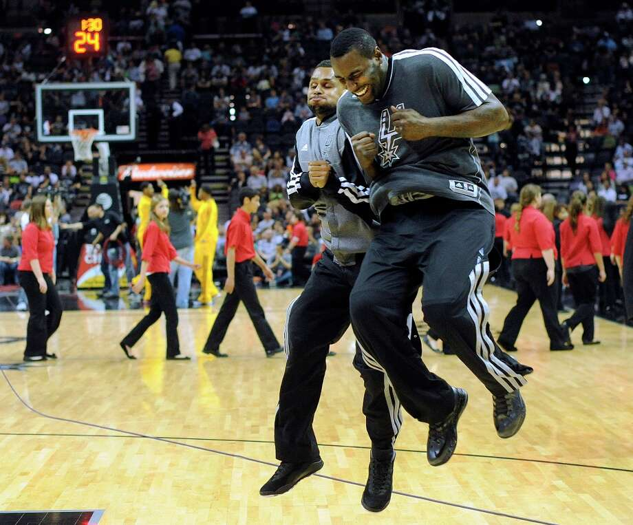 Patty Mills (left) and DeJuan Blair of the Spurs enjoy themselves during warmups before the team's victory over the Cleveland Cavaliers on Saturday, March 16, 2013. Photo: Billy Calzada, San Antonio Express-News / San Antonio Express-News