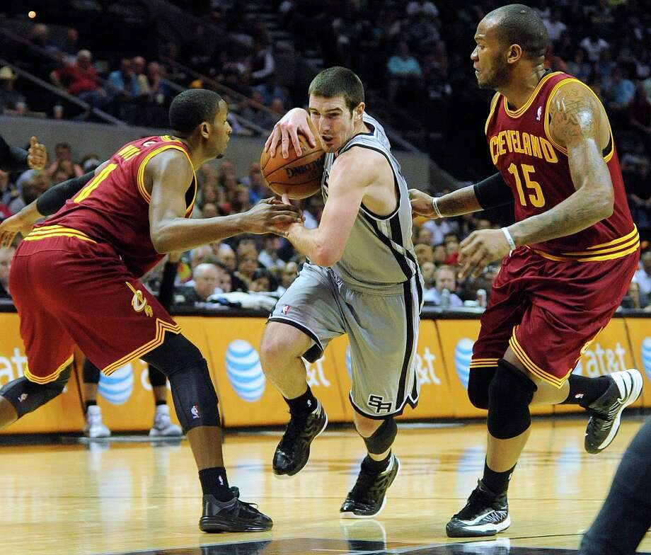 Nando De Colo of the Spurs drives between C.J. Miles, left, and Marreese Speights of the Cleveland Cavaliers during first-half action at the AT&T Center on Saturday, March 16, 2013. Photo: Billy Calzada, San Antonio Express-News / San Antonio Express-News