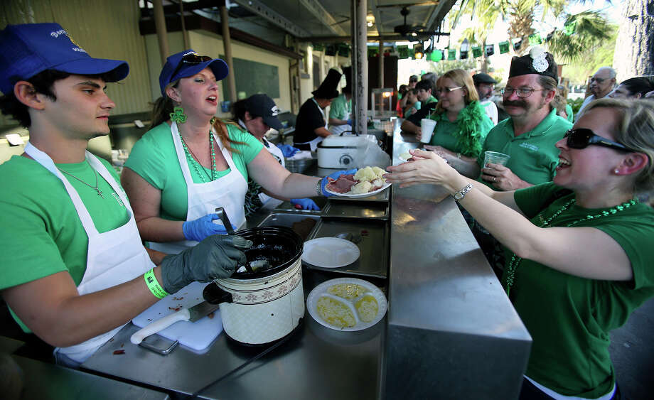 Keri Robertson is handed a plate of traditional Irish food as St. Patrick's Day is celebrated at Beethoven Hall on  March 16, 2013. Serving are Daryl Mcghiey and Briana Carpenter.  Behind Robertson is David Sutherland. Photo: Tom Reel, San Antonio Express-News