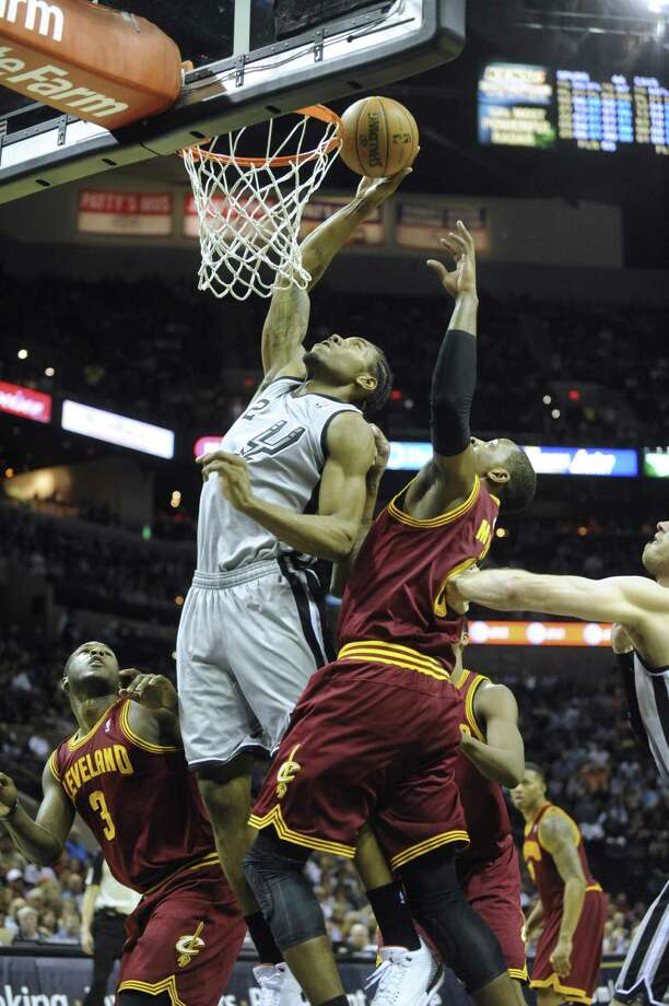 Kawhi Leonard tips in a miss as the Cavs' C.J. Miles (right) and Dion Waiters look on. Photo: Billy Calzada / San Antonio Express-News