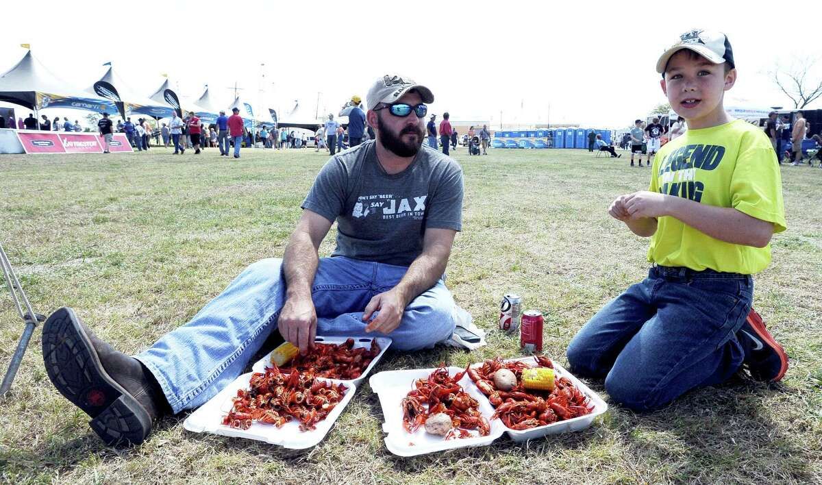 Chris and Conner Buxton enjoy crawfish from Spankys Bar and Grill in Orange during the 2013 Orange County River Festival. Photo taken: Randy Edwards/The Enterprise