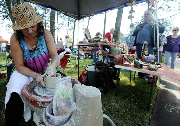 Cynthia Grimes works on a piece of pottery at her booth during the Art in the Park event at Stark Park in Orange during the 2013 Orange County River Festival. Photo taken: Randy Edwards/The Enterprise