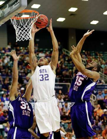 Stephen F. Austin's Taylor Smith (32) shoots as Northwestern State's DeQuan Hicks, left, and O.J. Evans (35) defend during the first half of the Southland Conference championship NCAA college basketball game, Saturday, March 16, 2013, in Katy, Texas. (AP Photo/David J. Phillip) Photo: David J. Phillip, Associated Press / AP