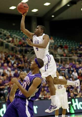 Stephen F. Austin's Hal Bateman (4) jumps to shoot as Northwestern State's Patrick Robinson (10) defends during the first half of a Southland Conference championship basketball game on Saturday, March 16, 2013, in Katy, Texas. (AP Photo/David J. Phillip) Photo: David J. Phillip, Associated Press / AP