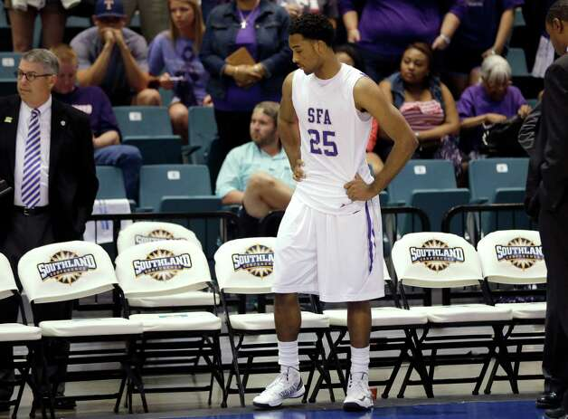 Stephen F. Austin's Desmond Haymon stands by his bench as Northwestern State players celebrate after the Southland Conference men's tournament title match-up Saturday, March 16, 2013, in Katy, Texas. Northwestern State won 68-66 in the NCAA college basketball game. (AP Photo/David J. Phillip) Photo: David J. Phillip, Associated Press / AP