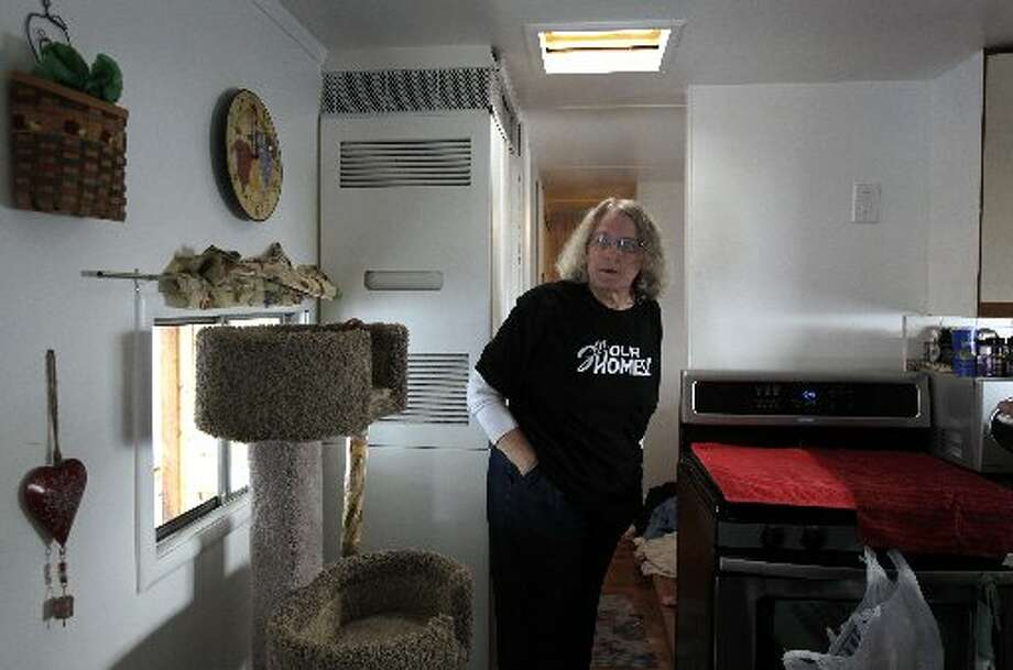 Melodie Cheney walks through the kitchen of her single-wide trailer at the Buena Vista mobile home park in Palo Alto, Calif. on Thursday, March 14, 2013. The owners of the property have applied for permission from the city to close it, sell the land to a big developer and evict the residents of the 117 homes on the site.