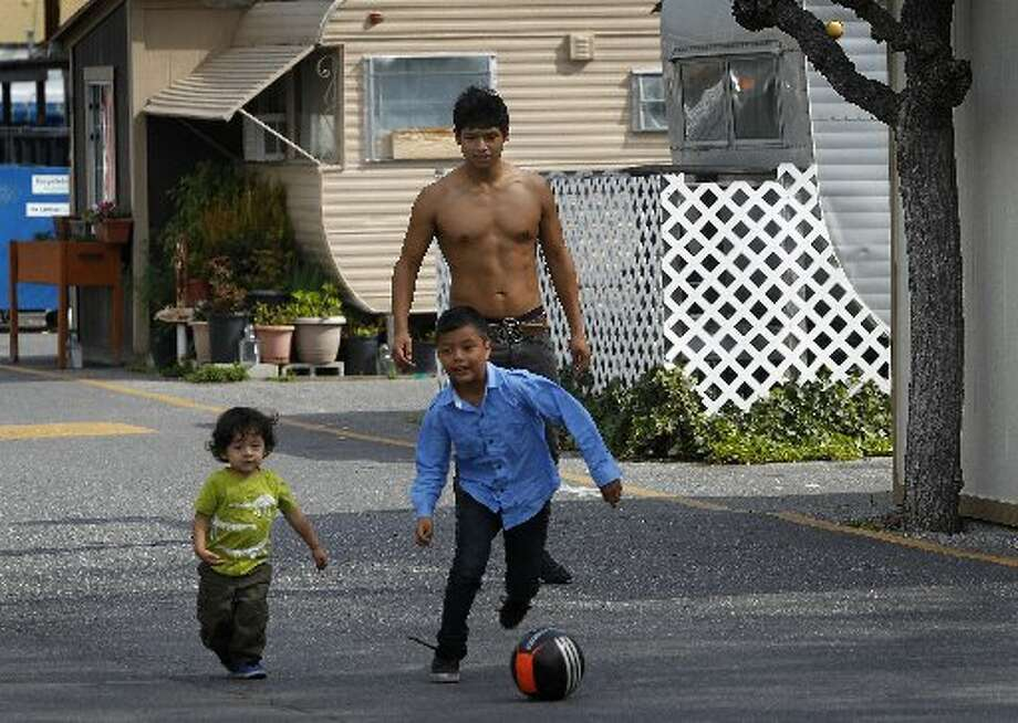 Giovanni Vargas (rear) plays soccer with his son Leo, 2, (left) and neighbor Miguel Landa, 7, at the Buena Vista mobile home park in Palo Alto, Calif. on Thursday, March 14, 2013. The owners of the property have applied for permission from the city to close it, sell the land to a big developer and evict the residents of the 117 homes on the site.