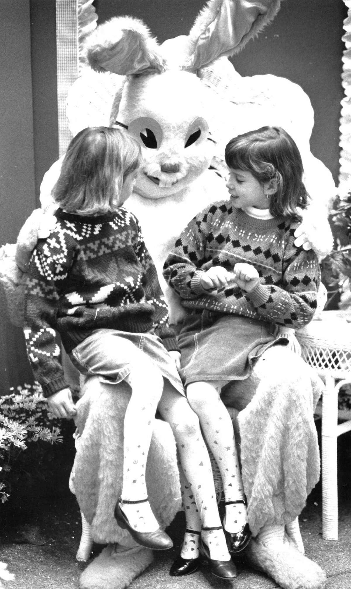 Easter bonnets and chocolate eggs might be the topic of conversation as Vanessa, 5, left, and Jordana Scanlan, 6, meet the Easter Bunny (Kevin Myer) at the Stamford Town Center on March 19, 1988.