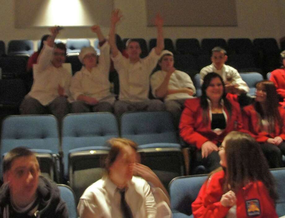 Culinary students wave to the camera. Photo by Amanda Pellegrin for New Visions: Journalism & Media Studies.