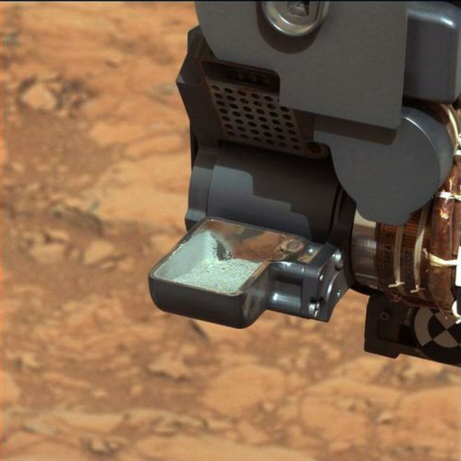 This image released by NASA shows the Curiosity rover holding a scoop of powdered rock on Mars. The rover recently drilled into a Martian rock for the first time and transferred a pinch of powder to its instruments to analyze the chemical makeup. NASA scientists reported that the result proved that conditions on ancient Mars could have sustained life. Photo: AP