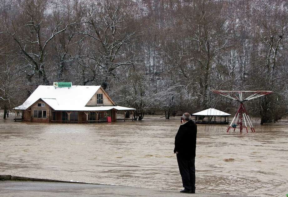 A man looks at flooded houses pictured in the village of Guri i Zi , in the western part of Kosovo on Friday. A 8-year-old girl drowned after days off heavy rain fall swelled a river in the northern town of Skenderaj, and  flooded many areas in Kosovo. Photo: AP