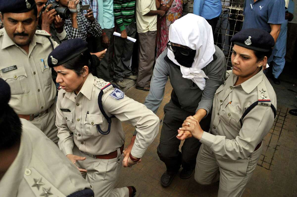 A Swiss woman, center, who, according to police, was gang-raped by a group of eight men while touring by bicycle with her husband, is escorted on Saturday by policewomen for a medical examination at a hospital in Gwalior, in the central Indian state of Madhya Pradesh. Indian police said they arrested five men on Sunday in connection with the gang rape.