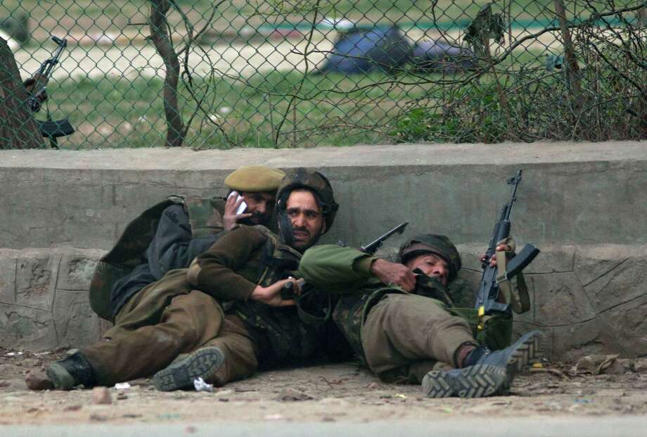 Indian police men take cover during a gun battle in Srinagar, India, Wednesday. A team of militants stormed a paramilitary camp Wednesday morning in the capital of Indian-controlled Kashmir, leaving five soldiers and two militants dead and 10 more people wounded, a police official said. Photo: AP