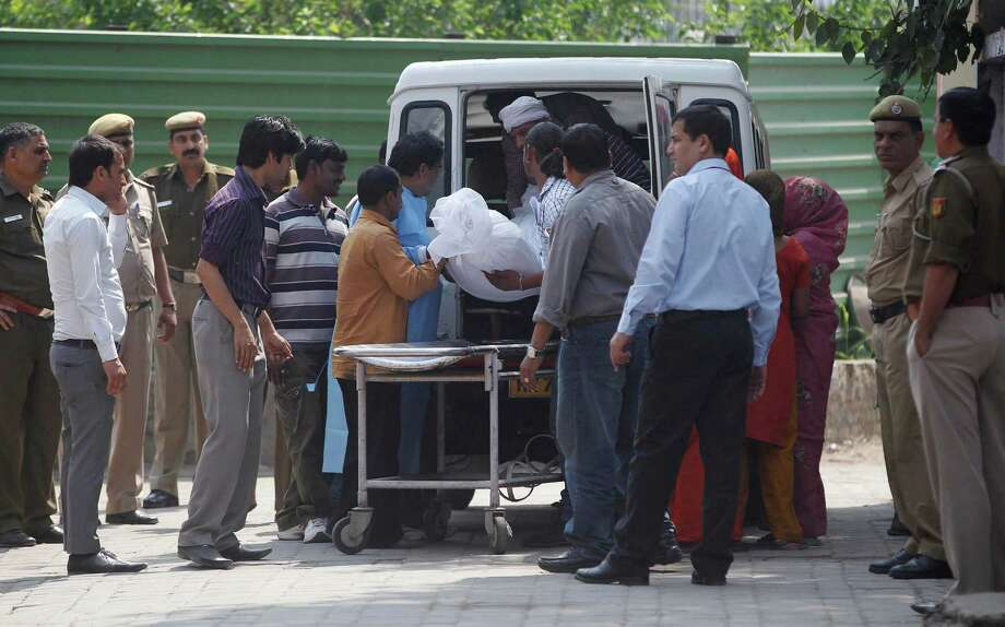 Unidentified relatives of Ram Singh, one of the men on trial for his alleged involvement in the gang rape and fatal beating of a woman aboard a New Delhi bus, carry Singh's body in to a waiting hearse outside a mortuary in New Delhi, India, Tuesday. The body of the man who died in a New Delhi jail while in the midst of a high-profile rape trial was released to his family Tuesday after a post-mortem exam aimed at determining whether he committed suicide or was killed. Photo: AP