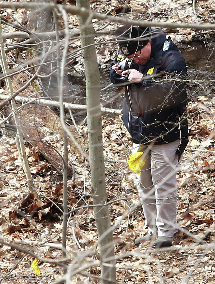 A Vernon police detective photographs evidence where a human skull was discovered Thursday in Vernon, Conn. Police say it's too early to tell whether the remains are those of anyone in a missing person case. Local residents are wondering if the remains are those of one of three girls who disappeared in the late 1960s and early 1970s. (AP Photo/Journal Inquirer, Jared Ramsdell) Photo: AP