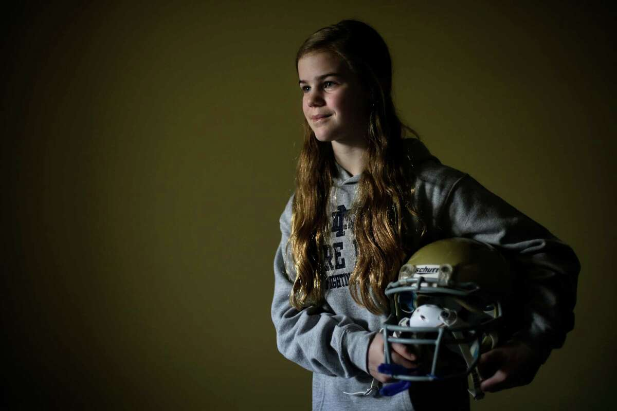 Caroline Pla, 11, poses for a photo with her helmet in Doylestown, Pa., last month. The archbishop of Philadelphia announced Thursday that he'll allow the region's Catholic youth sports league to field coed football teams. The Pla family had been fighting the Roman Catholic Archdiocese of Philadelphia for the right to continue playing church sponsored youth football.