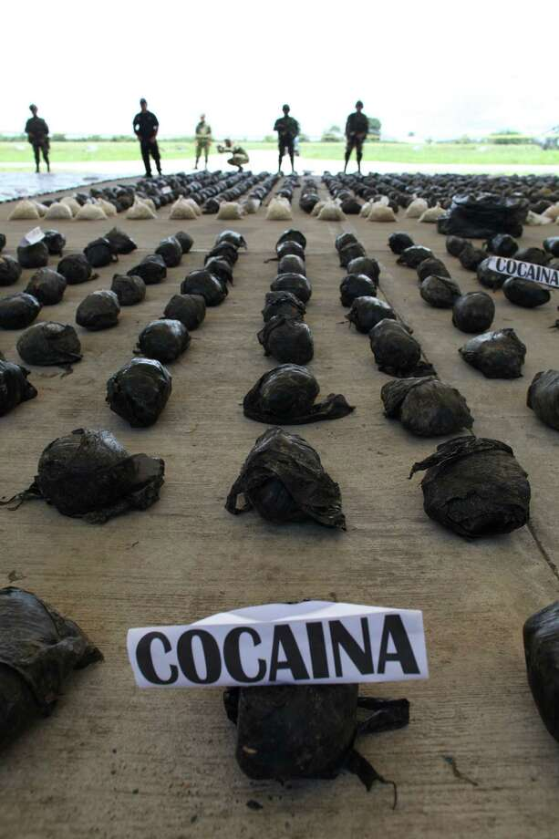 Soldiers guard bags containing cocaine displayed for the press at the airport in Tumaco, Colombia, on Saturday. According to Col. Jorge Mora, commander of an Army counter narcotics brigade, troops seized 3.9 tons of cocaine that belonged to rebels of the Revolutionary Armed Forces of Colombia, FARC,  in a jungle area near Timbiqui, on Colombia's southern Pacific coast. Photo: AP