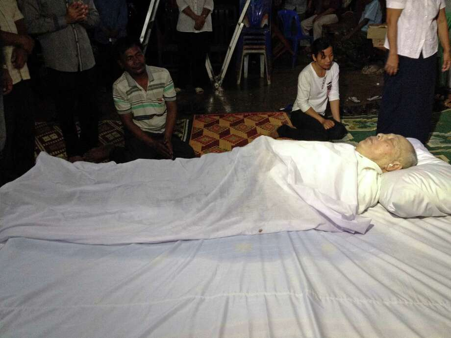 Relatives sit next to the body of Ieng Sary after he died at a hospital in Phnom Penh, Cambodia, on Thursday. Ieng Sary, who co-founded the communist Khmer Rouge regime responsible for the deaths of an estimated 1.7 million Cambodians in the 1970s, and who decades later became one of its few leaders to be put on trial, died Thursday before his case could be finished. He was 87. (AP Photo/Documentation Center of Cambodia)  Photo: AP