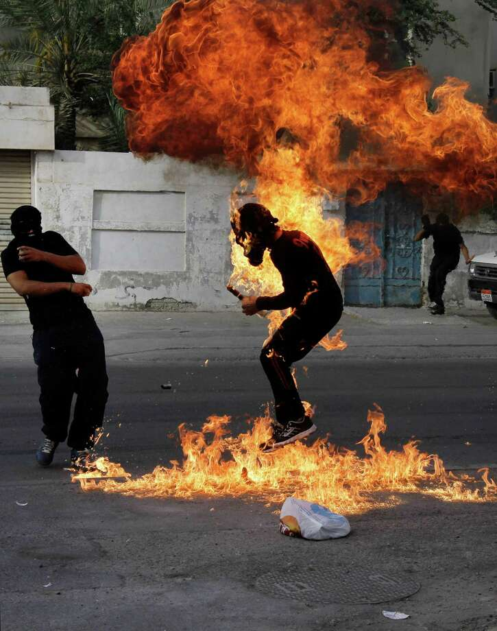 A Bahraini anti-government protester is engulfed in flames when a shot fired by riot police hit the petrol bomb in his hand that he was preparing to throw during clashes in Sanabis, Bahrain, Thursday. Photo: AP