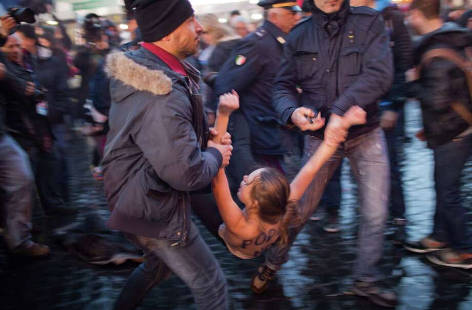An Femen group activist is detained by police officers following a protest against the pope outside St. Peter's Square as cardinals took an oath in the Sistine Chapel at the start the conclave to elect a new pope at the Vatican.  Photo: AP
