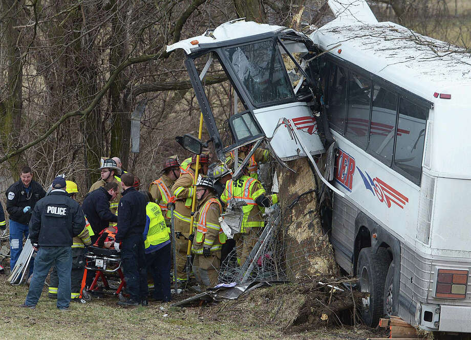Emergency and rescue crews respond to the scene of a tour bus crash on the Pennsylvania Turnpike on Saturday near Carlisle, Pa.  The tour bus was carrying a college's women's lacrosse team to a game when it went off the Pennsylvania Turnpike and crashed into a tree, killing a pregnant coach and the driver and sending others to hospitals, authorities said. Photo: AP