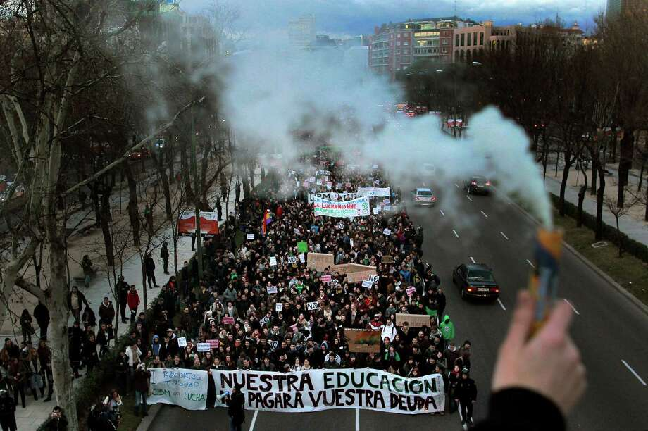 "A man holds smoke flare as students march during a protest as a part of an university students strike against financial cuts on education and in defense of the public education in Madrid, Spain, Thursday. The banner in foreground read ""Our Education will pay your debts."" Photo: AP"