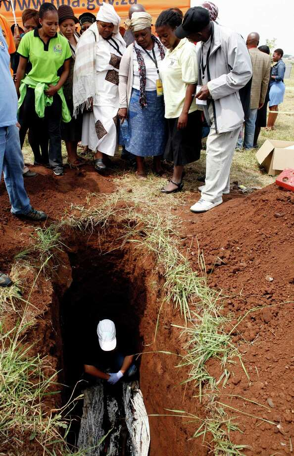 Dorothy Sono, center wearing blue skirt, with relatives surrounding the presumed grave of her son Lolo Sono, as forensic officer inspects a skeletal remains at Avalon Cemetery in Johannesburg, South Africa, on Tuesday. Forensic scientists on Tuesday exhumed two bodies believed to belong to young activists last seen 24 years ago at the home of Winnie Madikizela-Mandela, a discovery that has forced a new police murder investigation. Photo: AP