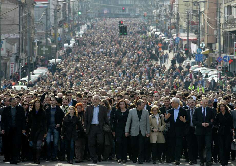 People march down a street to pay their respect at a memorial service marking the 10th anniversary of the assassination of the first democratic prime minister Zoran Djindjic, in Belgrade, Serbia, Tuesday. More than 15,000 people have joined a march honoring Serbia's slain prime minister Zoran Djindjic, in an outpouring of grief for the reformist leader who launched the Balkan country's bid to reconnect with the world after the wars of the 1990s. Djindjic was killed by a sniper shot in March 2003 in front of the government headquarters in central Belgrade. More than a dozen nationalist paramilitaries and criminals have been convicted and sentenced for the killing. Photo: AP
