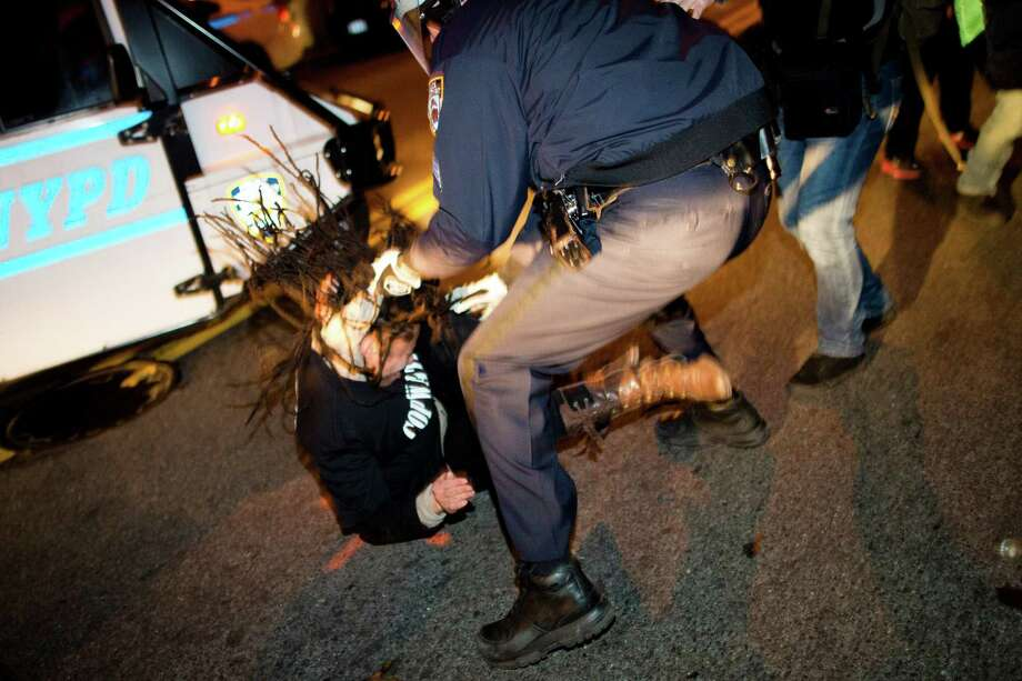 "A demonstrator is thrown to the ground by her hair during a march following a vigil held for Kimani ""Kiki"" Gray in the East Flatbush neighborhood of New York's Brooklyn borough, Wednesday, March 13, 2013, in New York. According to the NYPD, the teen pointed a .38-caliber revolver at the plainclothes officers, who responded by shooting him to death. Photo: AP"