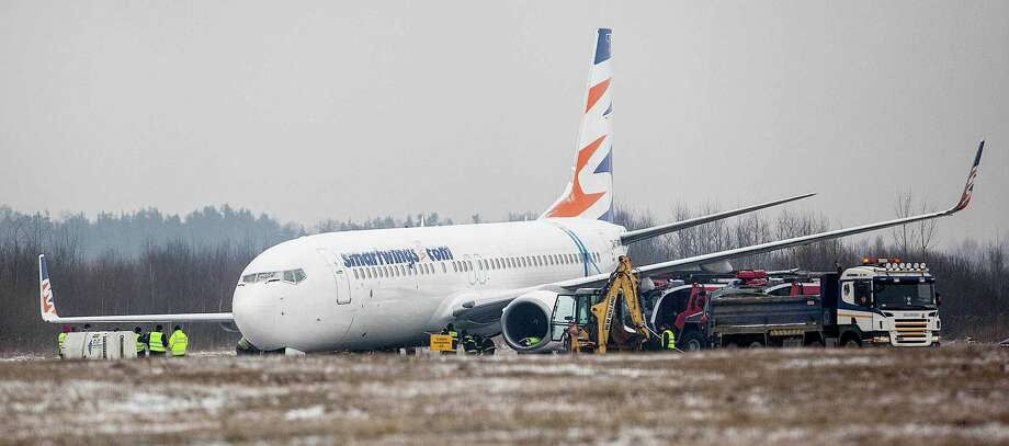 Teams of Czech and Polish experts are working to free a Czech Boeing 737 airplane from a muddy field at the airport in Katowice, Poland on Wednesday. The plane from the Czech Travel Service airline skidded late Tuesday and went some 22 yards off the Pyrzowice airport runway and ran into wet ground, where its front landing gear sank. None of the 176 passengers and six crew members was hurt. The airport remains closed and flights are redirected to nearby Krakow. (AP Photo/ Artur Gierwatowski)  Photo: AP